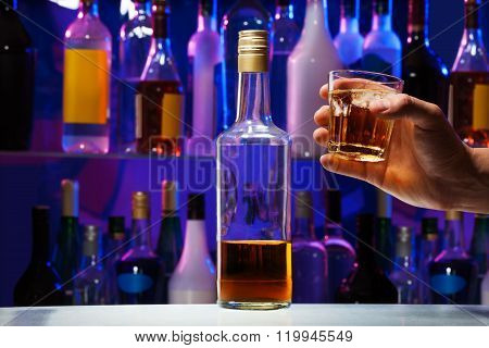 Whiskey bottle and glass in men's hand