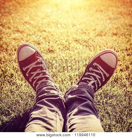 Closeup photo of lazy teen guy lying down on green grass and wearing stylish trendy gumshoes in bright yellow sunset light, body part, relaxing outdoors, fashion for hipster