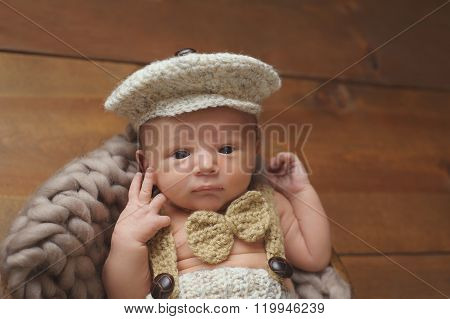 Newborn Baby Boy Wearing A Newsboy Cap And Bowtie