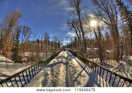 The sun over a snowy bridge road with a mountain landscape