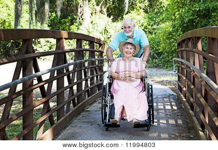 Senior man pushes his disabled wife through the park in a wheelchair.