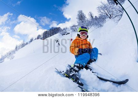 Child with ski  and wearing mask sit in snow