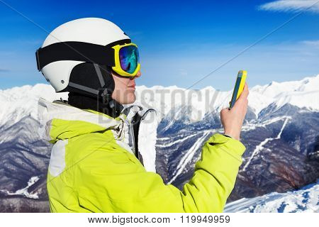 Skier woman with cell phone over mountains