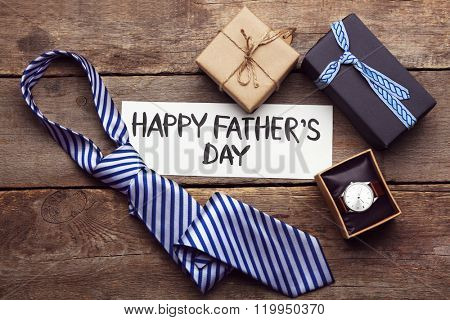 Happy Father's Day inscription with tie and watch on wooden background. Greetings and presents
