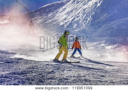 Mom and child ski down the piste teaching how to go down with sunlight lit through snow mist