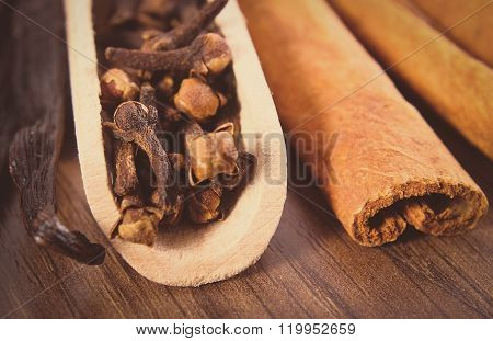 Vintage Photo, Closeup Of Cloves, Fragrant Vanilla And Cinnamon On Wooden Surface Plank