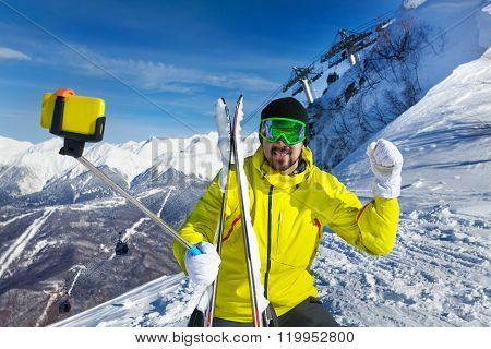 Happy skier man taking selfie on mountain