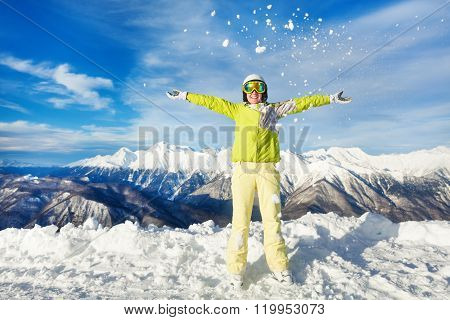 Happy skier woman throwing snow up