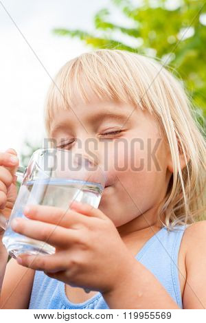 Blonde little girl wearing blue dress drinking water with her eyes closed in a summer garden