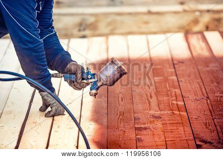 Industrial Worker Spraying Paint Over Timber Wood. Construction Worker With Spray Gun