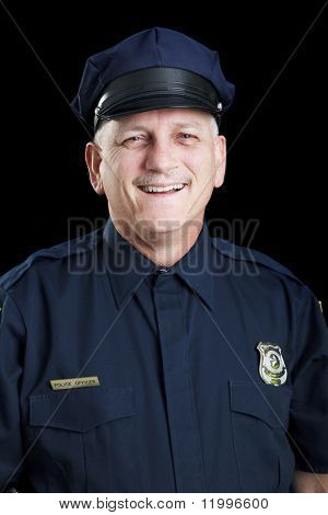 Portrait of friendly, smiling police officer on black background.