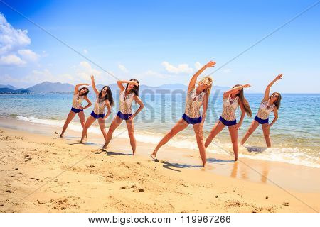Cheerleaders Stand In Triangle Hands Over Head On Wet Sand