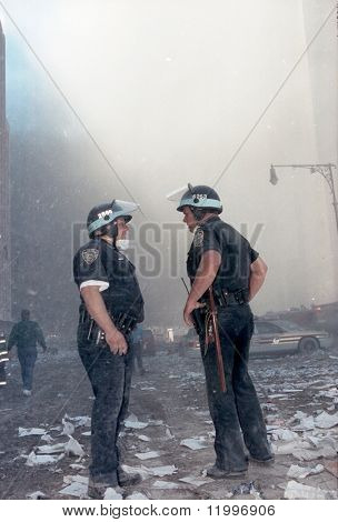 NEW YORK - SEPTEMBER 11:  Two New York City police officers speak to one another near the area known as Ground Zero after the collapse of the Twin Towers September 11, 2001 in New York City.