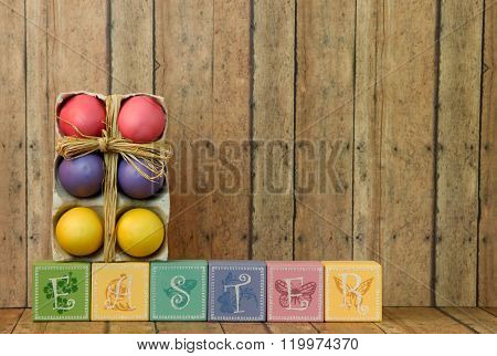 Colorful Easter Eggs And Easter Blocks On A Wood Background