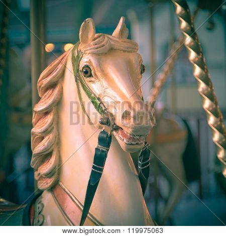 Head of horse in a merry go round on a historic summer funfair with vintage instagram look. Amusement concept