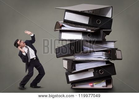 Busy businessman with a stack of files.