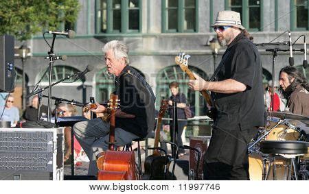NEW YORK - JULY 1: Bassist Marty Ballou (Center-R) performs with blues singer John Hammond (L) and keyboardist Bruce Katz (R) at Wagner Park on July 1, 2010 in New York City.