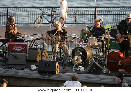 NEW YORK - JULY 1: Blues singer John Hammond (C) performs at Wagner Park with drummer Neil Gouvin (R) and keyboardist Bruce Katz (L) on July 1, 2010 in New York City.