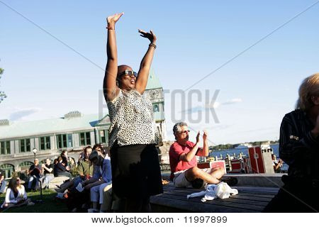 NEW YORK - JULY 1: A fan gestures excitedly as blues singer John Hammond performs at Wagner Park on July 1, 2010 in New York City.
