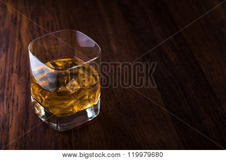 Glass of scotch whiskey and ice on a wooden background with copyspace