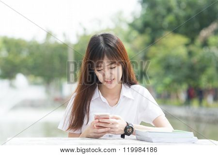 Asian Student With Uniform Using Smartphone In University