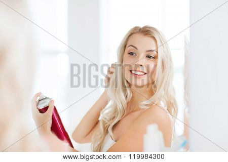 beauty, hygiene, hairstyle, morning and people concept - smiling young woman with hairspray styling her hair and looking to mirror at home bathroom