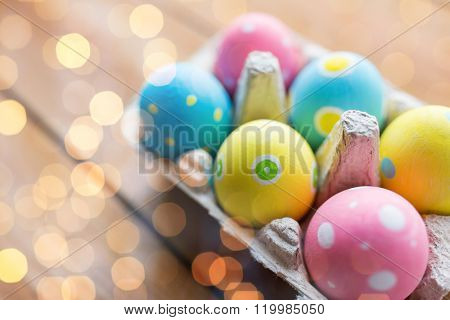 easter, holidays, tradition and object concept - close up of colored easter eggs in egg box or carton wooden surface over holidays lights
