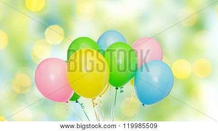 holidays, birthday, party and decoration concept - bunch of inflated colorful helium balloons over green summer lights background