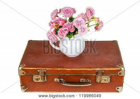 Pink flowers in jug on old brown vintage suitcase. Roses in jug. Pink roses. Shabby chic. Rustic con