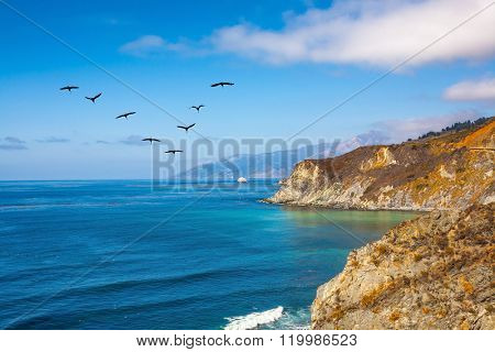 California State Route 1, USA. In the sky flies a flock of cranes. The scenic road passes over ocean bay with emerald water