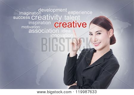 Businesswoman pointing at creative word on screen. business concept.