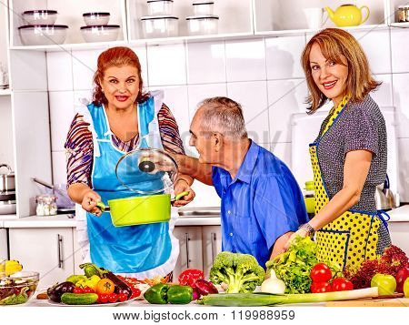 Big family cooking vegetarian soup at kitchen. Grandfather and grandmother.