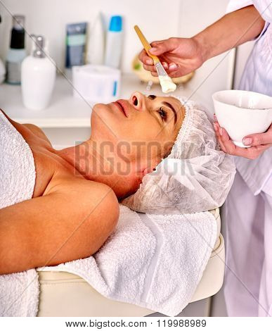 Woman with close up middle-aged take facial and neck clay mask in spa salon.