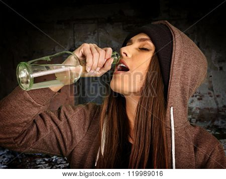 Drunk girl drink vodka from bottle of alcohol on  brick wall background. Soccial issue alcoholism.