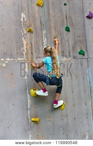 Young Girl Climbing A Wall