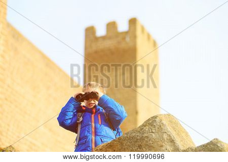 little boy looking through binoculars while travel
