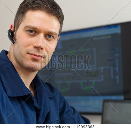 Male worker in thermal plant's control room.