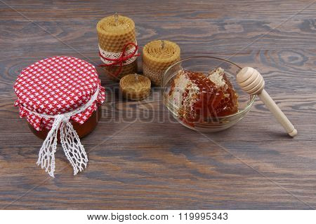 Homemade honey, honeycomb and beeswax candles on rustic wooden background