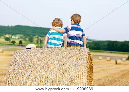 Two little children and friends with hay stack or bale