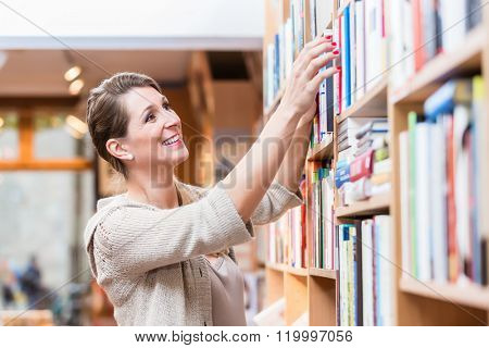 Woman choosing book in bookstore