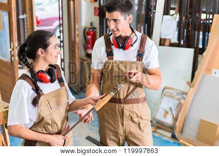 Team of carpenters comparing work pieces