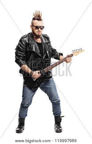 Full length portrait of a young male punk musician playing electric guitar isolated on white background