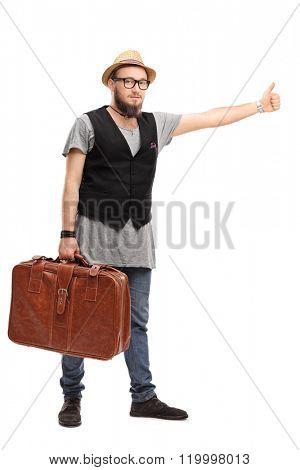 Full length portrait of a young hipster holding a brown suitcase and hitchhiking with his thumb isolated on white background