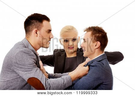 Businessmen getting into a fight woman trying to separate them