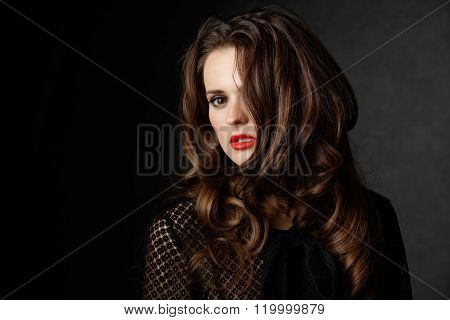 Woman With Curly Brown Hair Covering Half Face, Dark Background