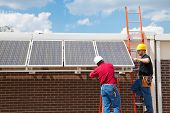 Workers installing solar panels on the side of a building.  Wide angle view with room for text.