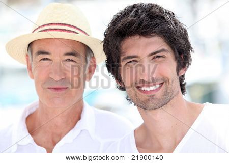 65 years old man wearing a straw hat and a 25 years old man posing in a summer vacation atmosphere