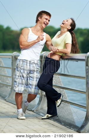 Young fitness couple of man and woman relaxing after jogging sport outdoors