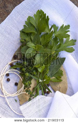 Bouquet garni of fresh herbs and peppercorns, on muslin ready for tying.