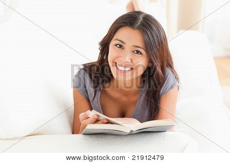 Cute Woman Holding A Book In Her Hand Ans Looking Into Camera